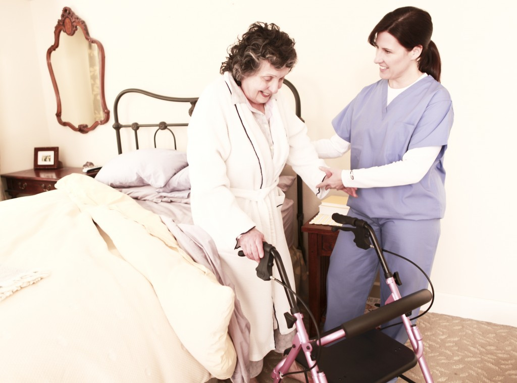 caregiver-helping-elderly-woman-recover-from-hospital